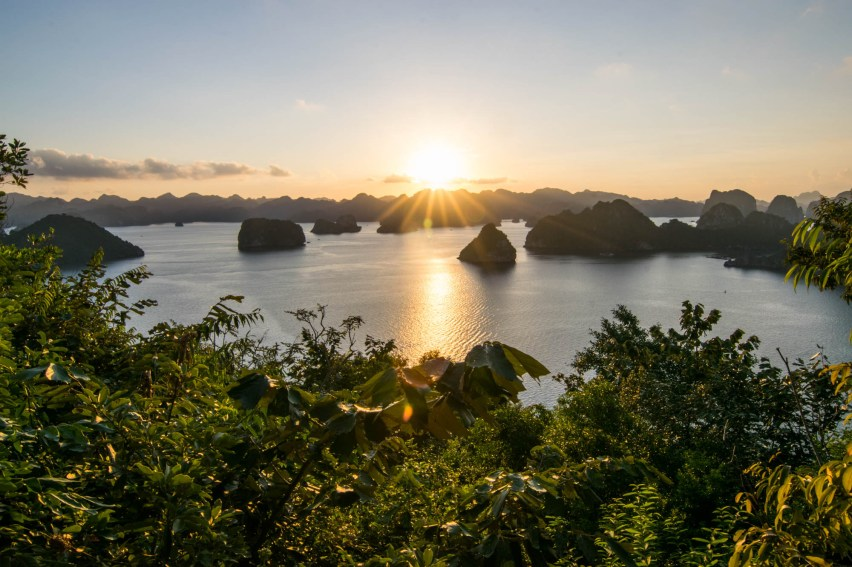 A collecrion of small islands are seen from a dense jungle as the sun sets and its rays fill Vietnam's Ha Long Bay.