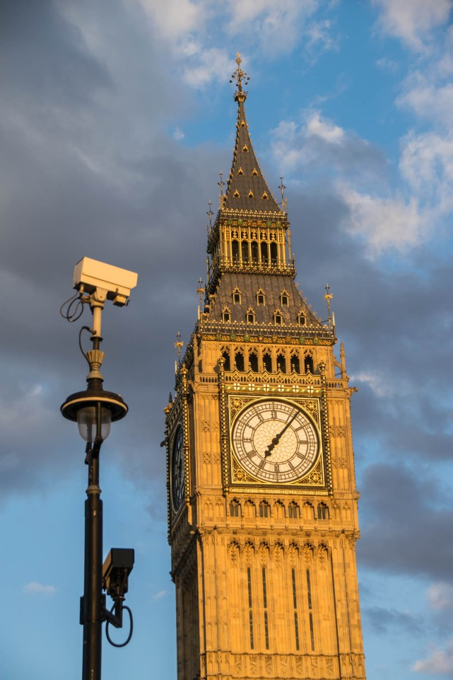 CCTV cameras on a street light are surveilling London streets. Big Ben clock tower is seen in the background as if it is being monitored.