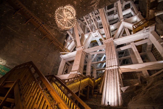 Underground wooden reinforcements painted in white are seen supporting part of the largest underground salt mine in poland, the Wieliczka salt mine. A chandelier hangs from the ceiling to add some class.