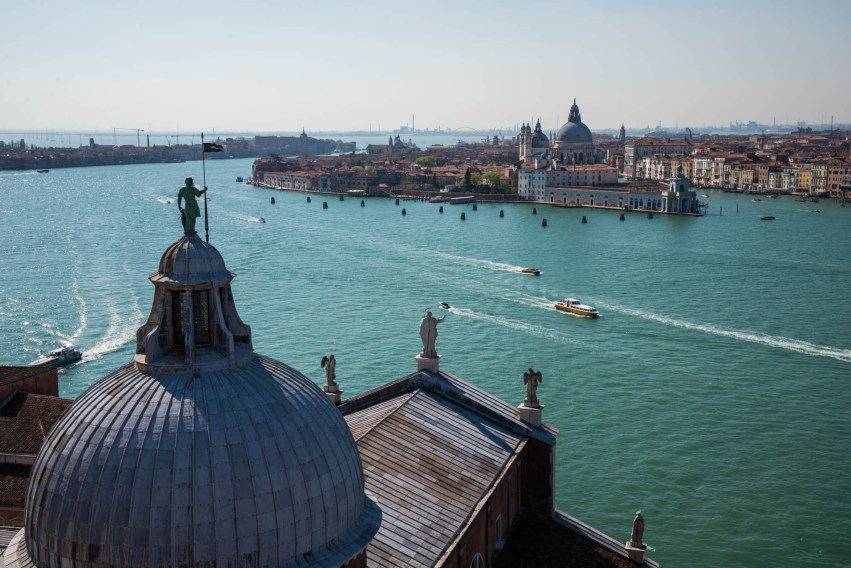 A statue on top of the Church of San Giorgio Maggiore is seen overlooking a large water way in Venice, Italy.