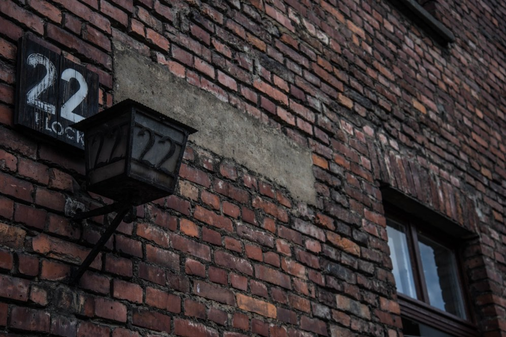 A sign and lamp notating block 22 are seen on the side of a brick building in the Auschwitz concentration camp.