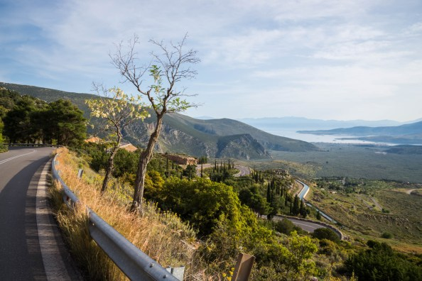 A greek mountain valley that leads to the Gulf of Corinth is seen from the side of a winding road lined with trees and shrubs.
