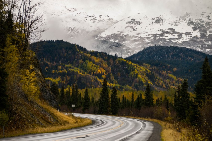 A wet winding road bends through an Alaskan autumn forest. Birch trees change to fall yellow colors. In the background behind clouds of fog mountains are seen with a light cover of snow.