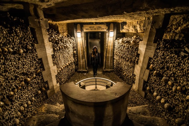 A young woman stands before a well in the underground catacombs of Paris. The walls are lined with human bones and skulls. She is hooded and wearing all black.