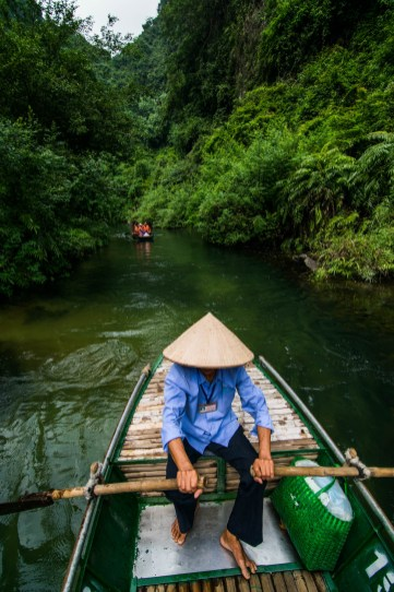 A barefoot guide in a traditional conical staw hat rows a boat along Ngo Dong, a river situated deep in the jungles of vietnam.