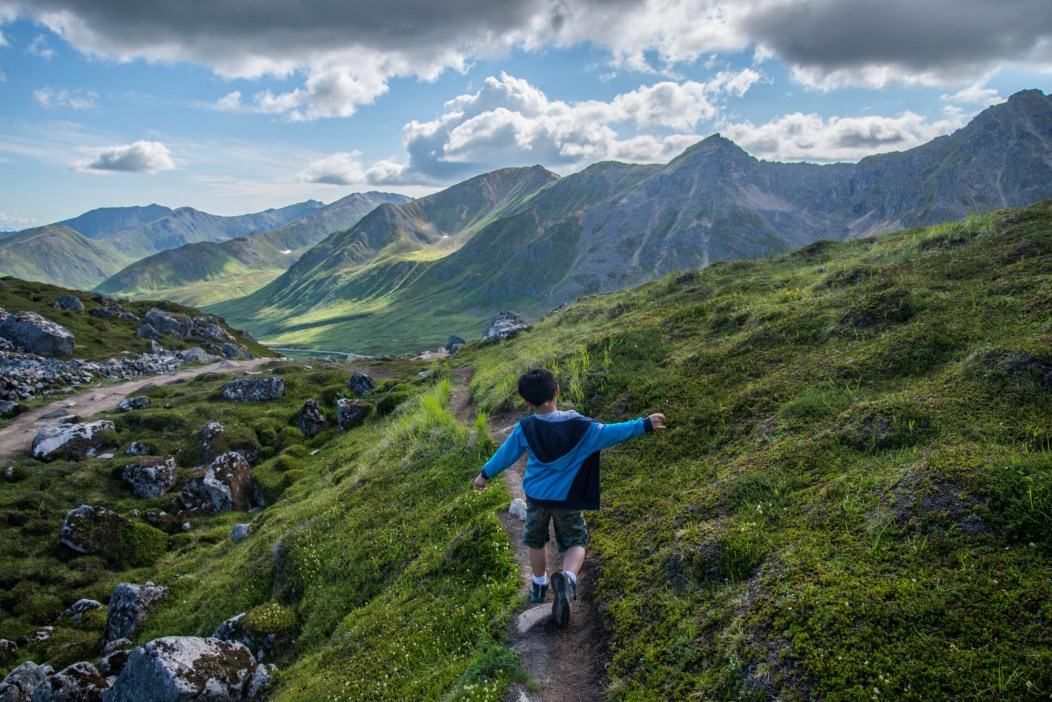 A young boy playfully runs down a spectacular alpine trail called Gold Chord Lake. He is using his arms to maintain balance. Its partly cloudy on a summer day in Alaska's Hatcher's Pass Mountains