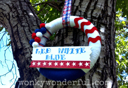 handmade wreath with red, white and blue yarn and a sign attached