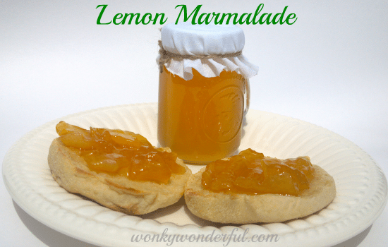 English muffins topped with lemon marmalade on white plate with jar of marmalade