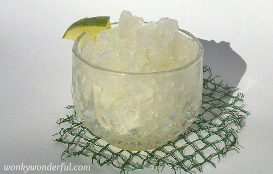 clear glass cup filled with slushy lime granita on green mesh