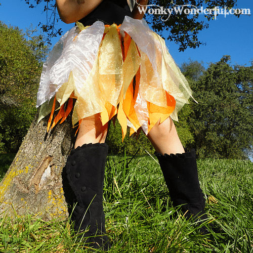 bottom view of little girl wearing a white, yellow and orange skirt made out of fabric scraps