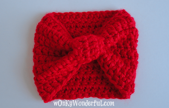 bright red crocheted cup cozy that looks like a bow
