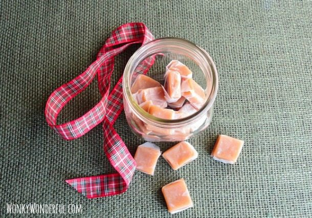 individually wrapped homemade caramels in glass jar with ribbon on the side
