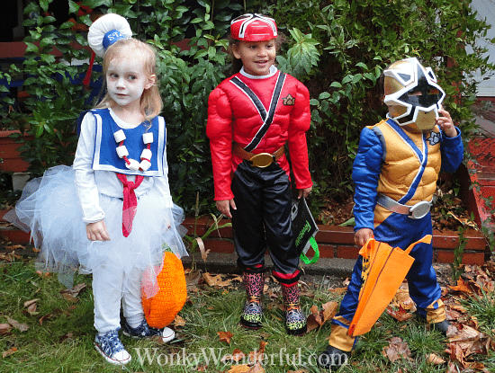 three kids dressed for halloween as a marshmallow man and two ninjas