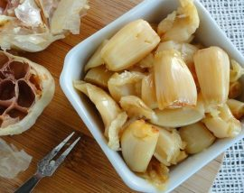 close up of roasted garlic cloves in white dish
