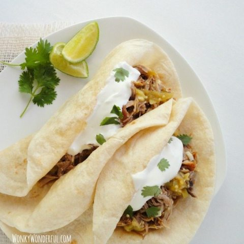 two tacos on white plate with cilantro and lime wedges on the side
