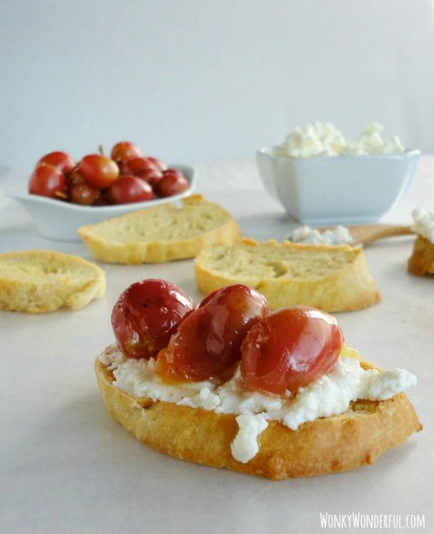 crostini topped with ricotta and cooked grapes, more ingredients unassembled in the background