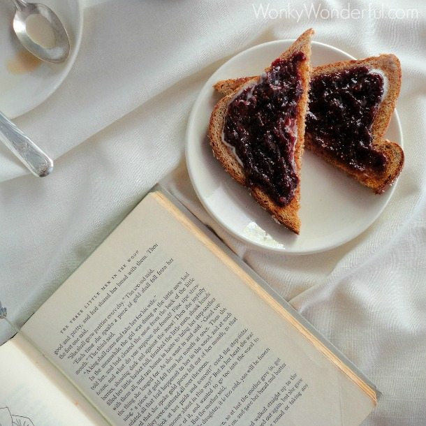 fig jam toast on white plate next to old book