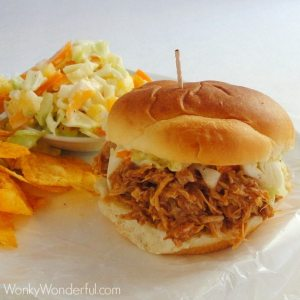 bbq chicken sandwich, slaw and chips on white plate