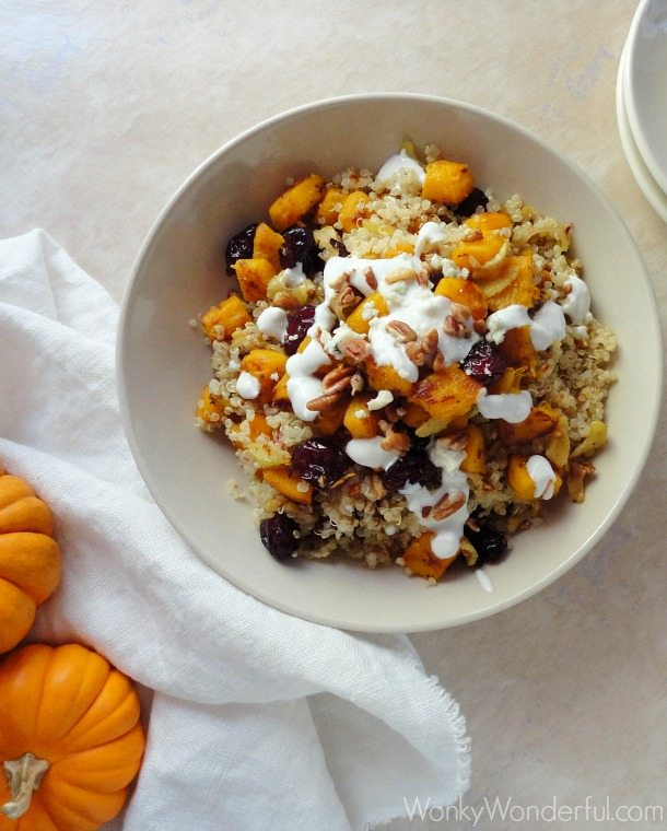 pumpkin quinoa in beige bowl next to plates and mini pumpkins