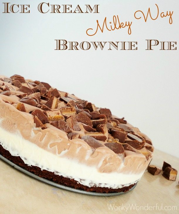 ice cream pie from the side showing layers of brownie, white ice cream, brown ice cream and chopped candy bars, photo text: ice cream Milky Way brownie pie