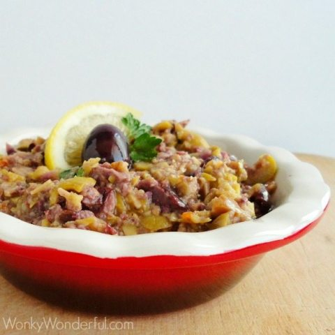 red dish filled with finely chopped olives topped with a lemon slice, olive and parsley