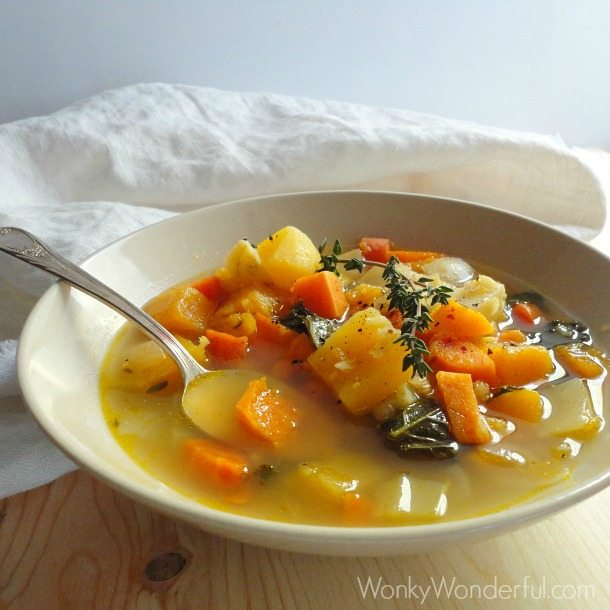 soup with orange and white vegetable chunks in beige bowl