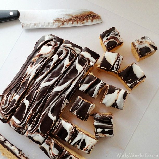 fudge being cut into squares on white cutting board with black handle knife