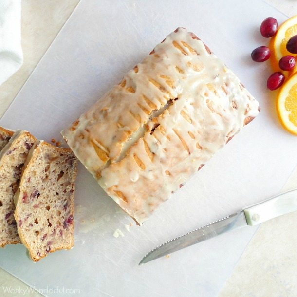 sliced cranberry loaf on cutting board next to white handle knife