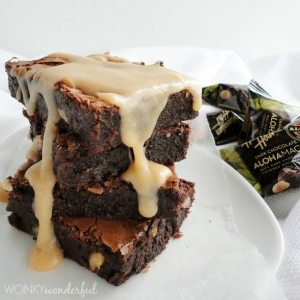 stack of chocolate brownies dripping with cream colored glaze