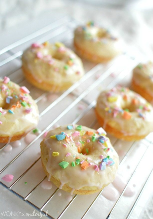 baked donuts topped with crushed candy on cooling rack
