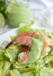 closeup of pink shrimp drizzled with light green dressing