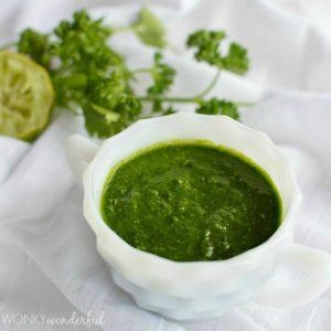 white dish filled with dark green sauce with fresh herbs on the side