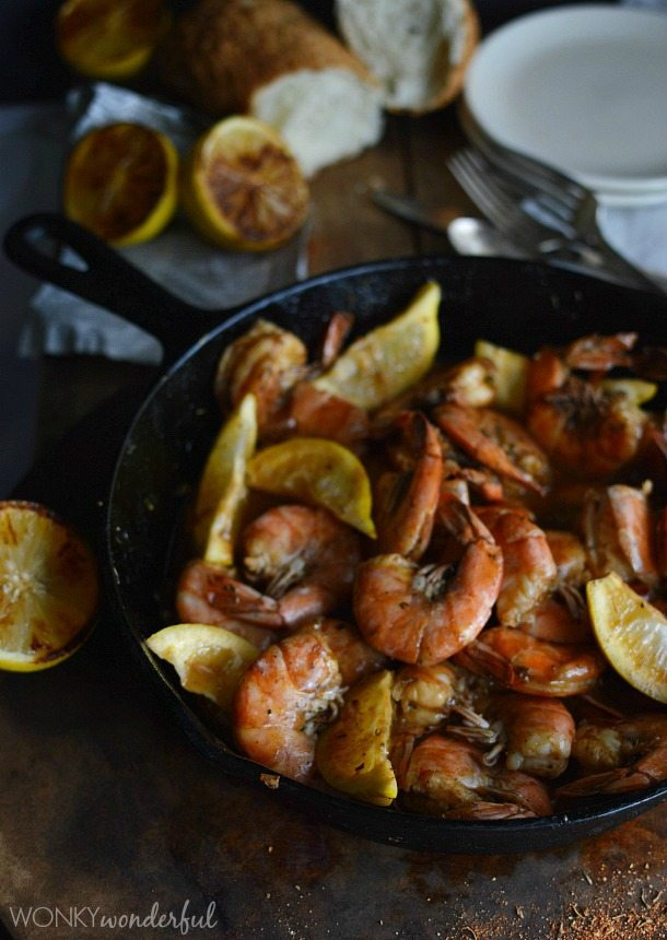 shrimp and lemons in cast iron pan with lemons and bread in the background