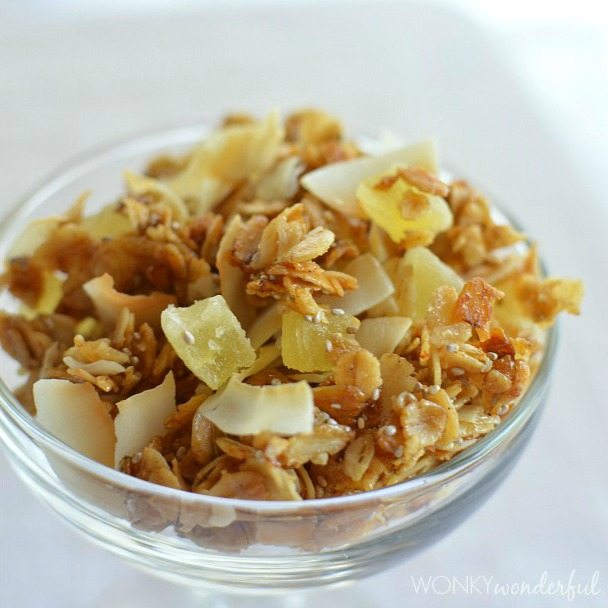 oat granola with pineapple and coconut chunks in clear glass bowl