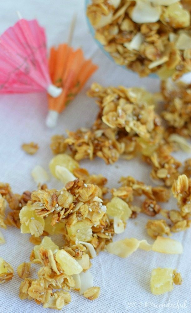 granola with dried pineapple chunks and coconut next to mini paper umbrellas