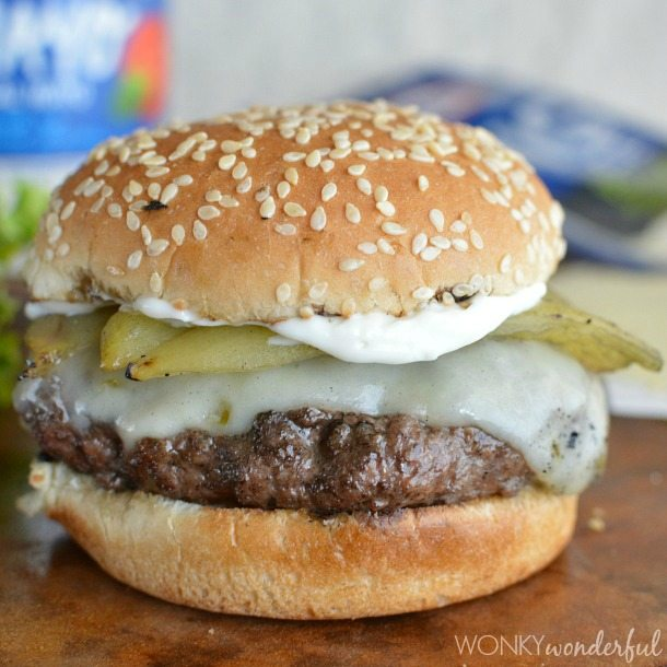 grilled burger with cheese and a green Chile on a sesame seed bun