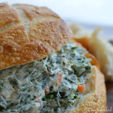 bread bowl filled with spinach dip and bread on top