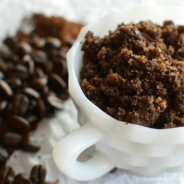 dark brown scrub in white dish next to coffee beans
