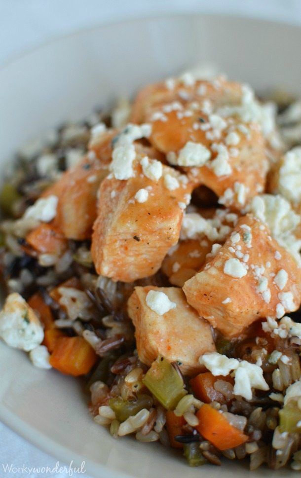 chicken pieces on rice with blue cheese crumbles and reddish orange sauce