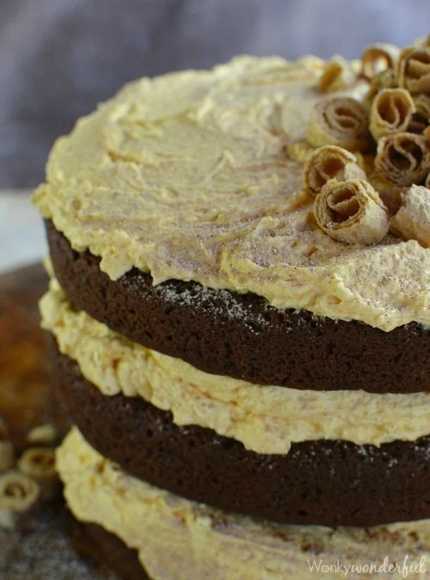 blown round cakes layered with yellowish frosting topped with spiral cookie pieces