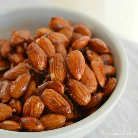 shiny reddish almonds in white bowl