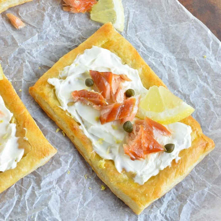 This Easy Smoked Salmon Appetizer Recipe begins with flaky puff pastry, topped with cream cheese, smoked salmon, lemon, capers and fresh dill. Perfect for an appetizer or breakfast!