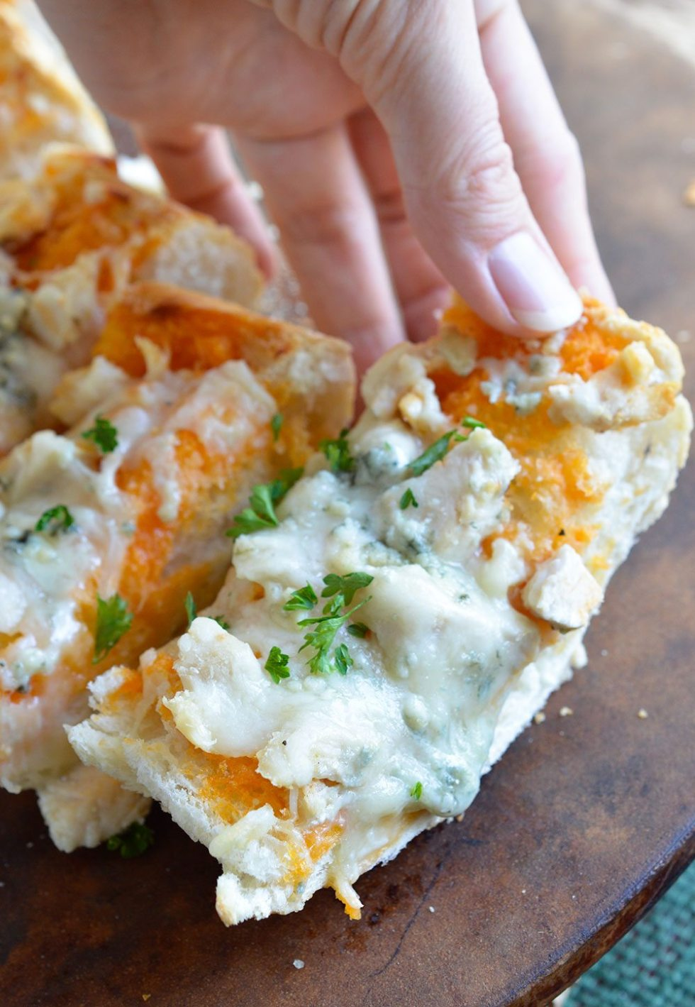 Buffalo Chicken Cheesy Bread is an easy and flavorful game day appetizer! Buffalo wing sauce, chicken and blue cheese come together in this hot, melty recipe.