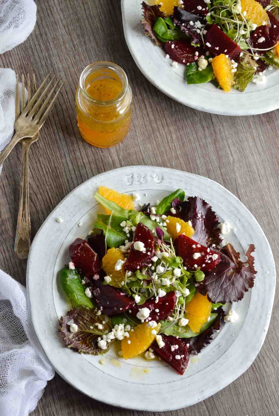 fresh beet salad on white plates with vinaigrette on the side