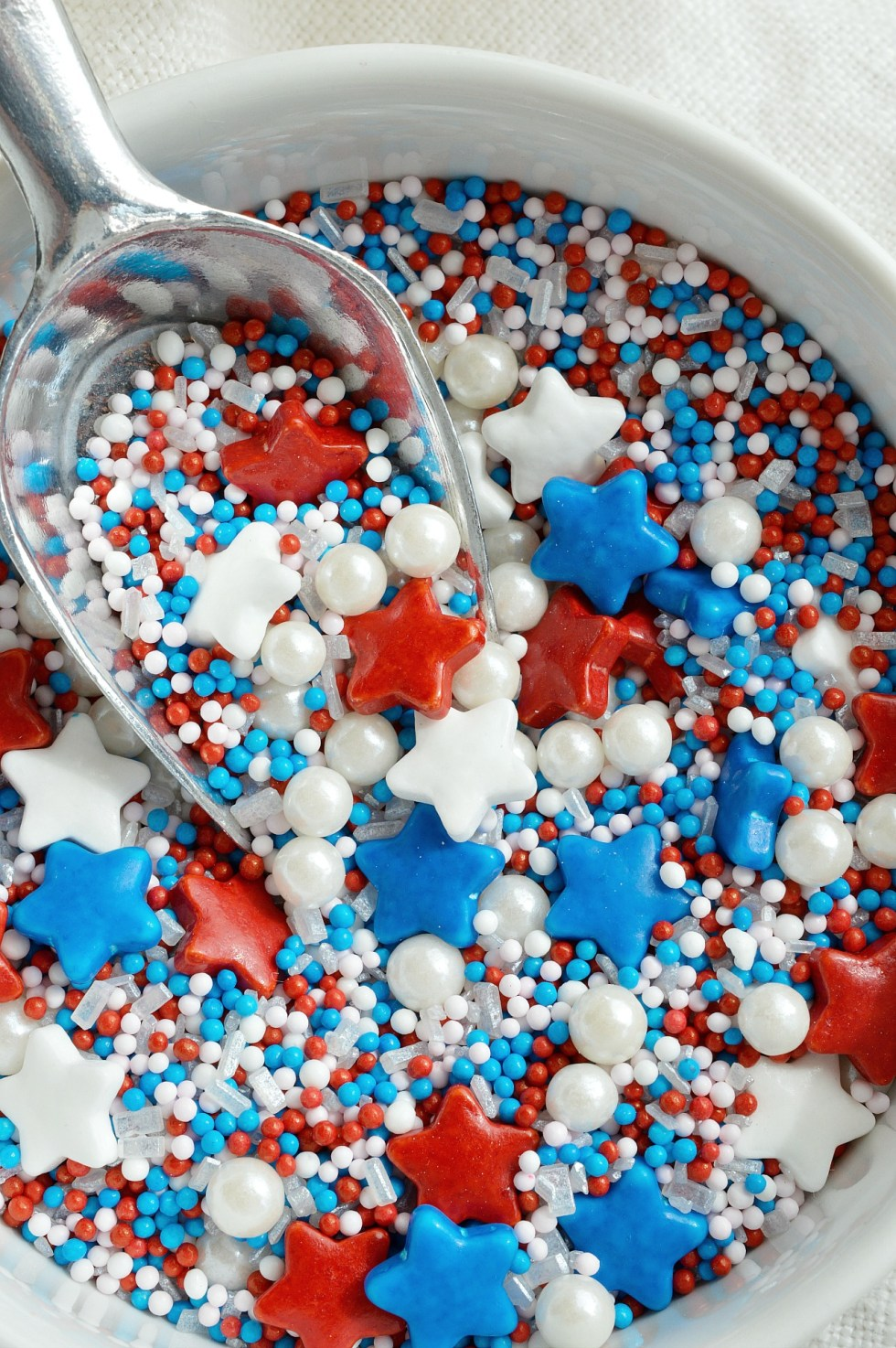 Make an easy and festive treat to enjoy while watching the fireworks. 4th of July Dessert Popcorn is popped microwave popcorn drizzled with white chocolate and topped with Red, White and Blue sprinkles! This patriotic dessert recipe is perfect for feeding a crowd!