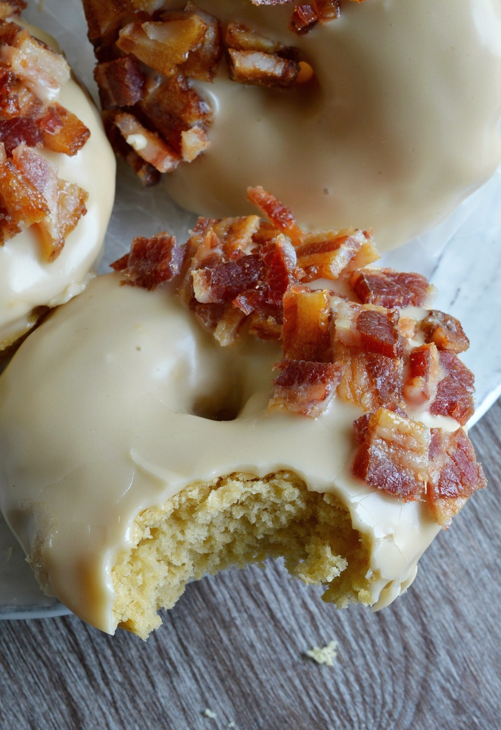These Maple Bacon Donuts have to be one of the best flavor combinations ever! Brown sugar and sour cream baked donuts with a pure maple syrup glaze then topped with brown sugar maple glazed bacon pieces. This breakfast recipe is the ultimate morning indulgence and perfection with a cup of coffee!