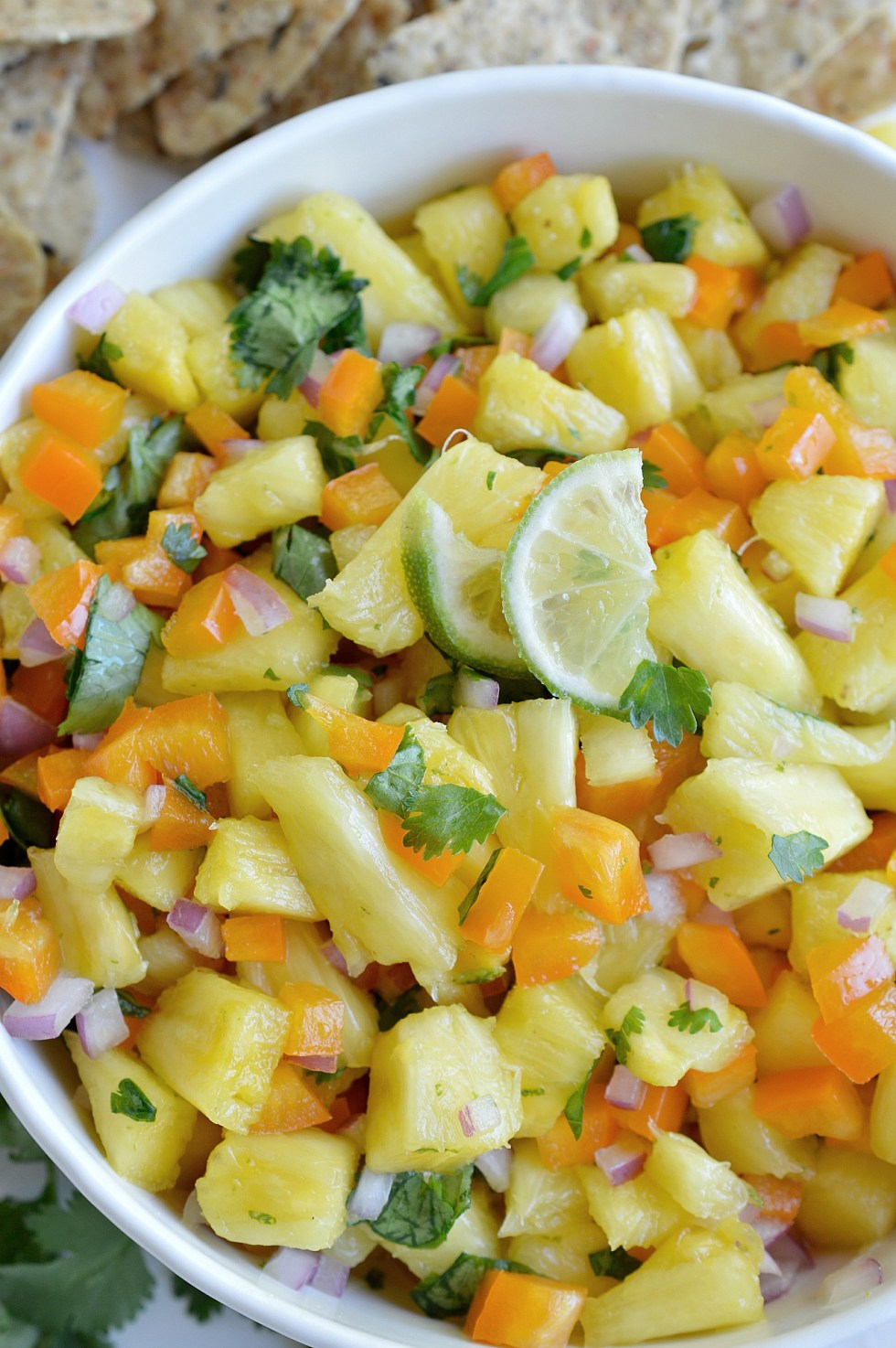 fresh bright yellow pineapple chunks mixed with cilantro, orange pepper, onion and lime
