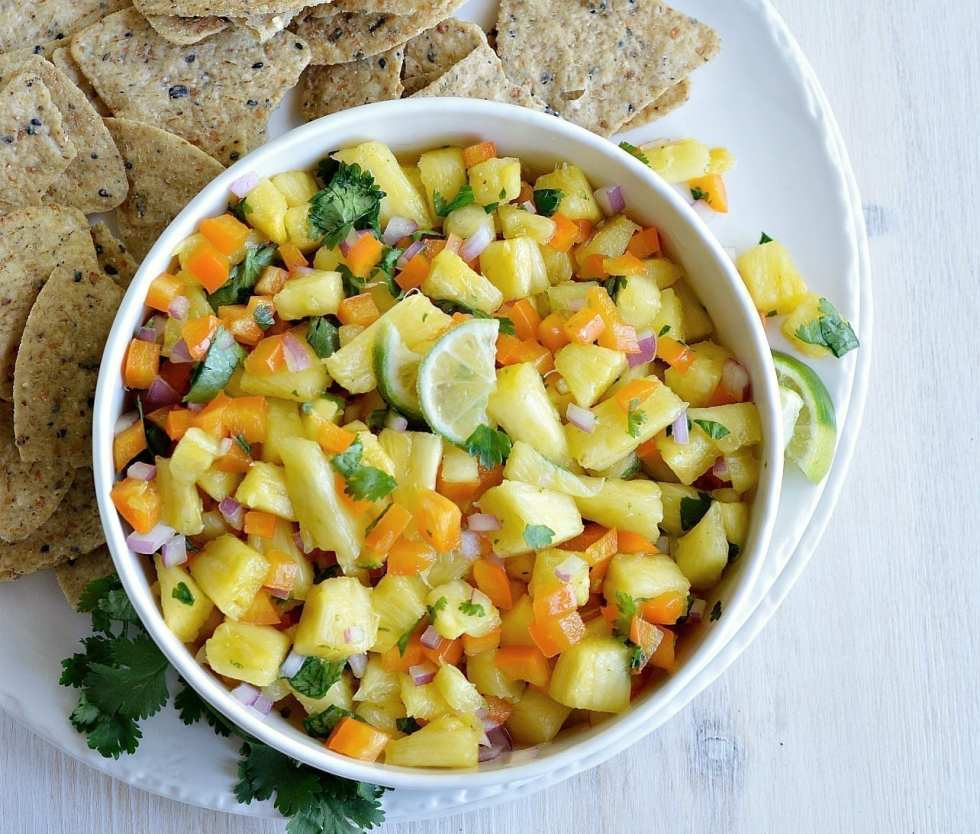 white bowl filled with fresh fruit salsa with chips on the side