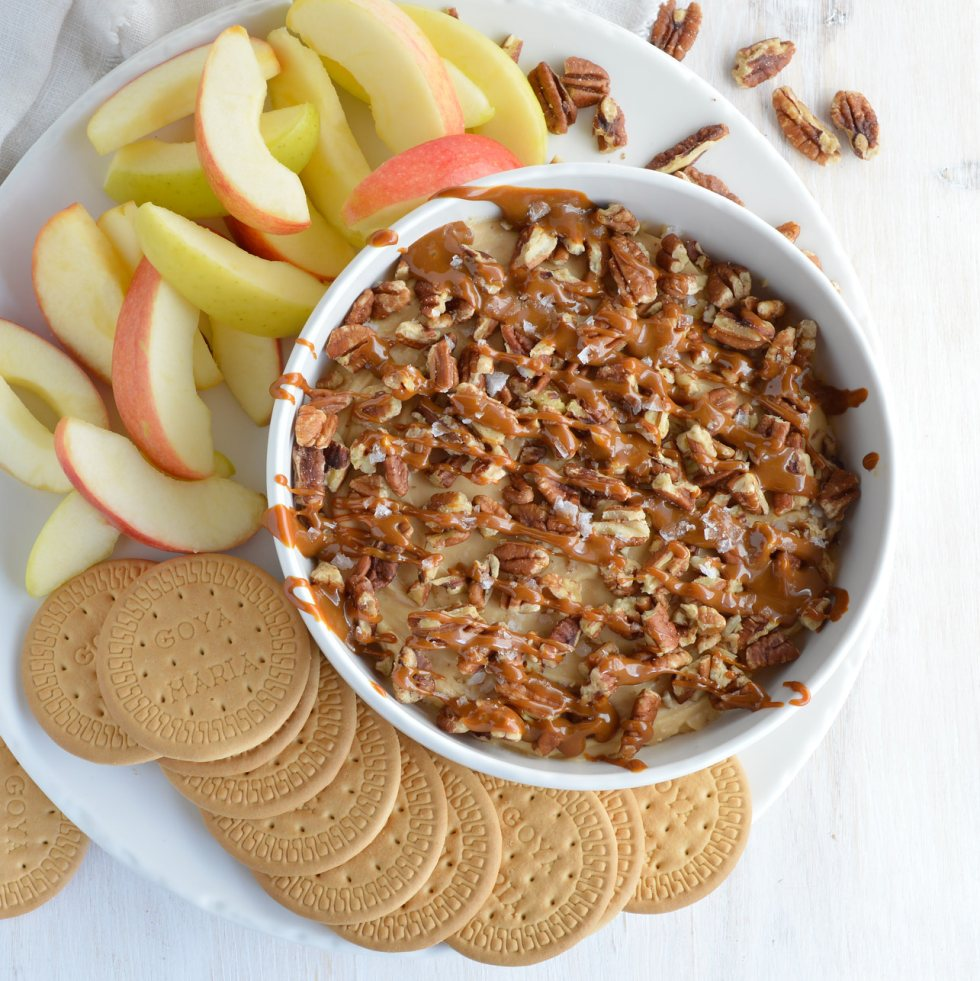 cheesecake dip in white bowl surrounded by apples and cookies