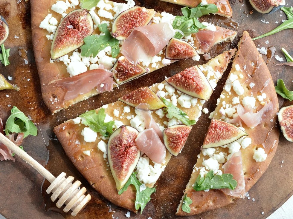 If you need a quick and easy dinner idea I am here for you! This Fig and Prosciutto Flatbread Pizza Recipe is a great no-fuss meal. Fresh figs, crumbled goat cheese, prosciutto, peppery greens, honey and flaked salt make this flatbread pizza ultra delicious . . . and perfect with a glass of wine!